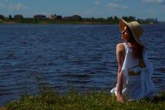 白色礼服的俏丽的妇女和魅力帽子在河沿,在背景的深大海放松 看远离照相机的女孩 免版税库存图片