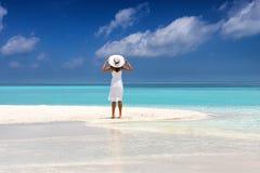 白色礼服的可爱的妇女在一个热带海滩站立 免版税库存图片
