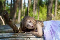 白色礼服的可爱的小女孩在森林森林若虫 晴朗的日 免版税库存图片