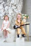 白色礼服的女孩和有吉他的流行音乐音乐家坐 免版税库存照片