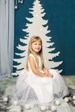 白色礼服的女孩在圣诞树的背景 库存照片