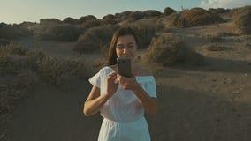 白色礼服的女孩在日落的电话做照片,在沙漠 温暖的夏天晚上,沙漠 慢的行动 影视素材