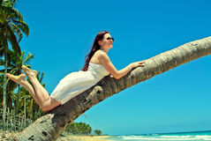 白色礼服的女孩在棕榈 库存照片