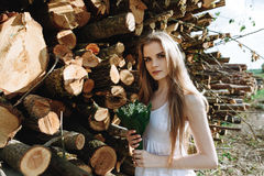 白色礼服的女孩在森林里在夏天 免版税库存照片
