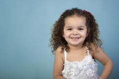 白色礼服的女孩在蓝色背景 免版税库存图片