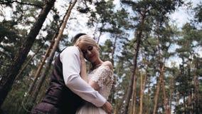 白色礼服的女孩按了她的头对她的男朋友的在爱立场的胸口A夫妇在一棵美丽的杉木f中间 股票视频