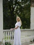 白色礼服的女孩是常设近的老扶手栏杆 库存照片