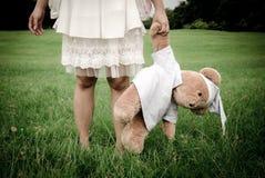 白色礼服的女孩有熊玩偶的。 库存照片
