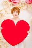 白色礼服的女孩有红色心脏的在手上 免版税库存图片