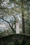 白色礼服的妇女在一座石桥梁 免版税图库摄影