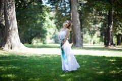 白色礼服的妇女在绿色公园 概念eco和平鸽子 免版税库存图片