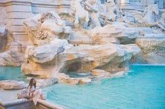 白色礼服的妇女在Trevi喷泉前面在罗马 库存照片