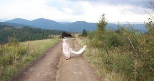 白色礼服的妇女微笑在她的跑掉沿在山的路的肩膀 股票视频