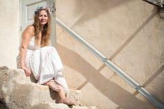白色礼服的妇女有头状花序带的 免版税库存图片