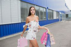 白色礼服的妇女有购物袋的 在买礼物以后的愉快的微笑 购买乐趣  图库摄影