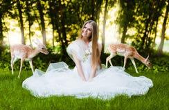 白色礼服的妇女有鹿的 免版税库存图片
