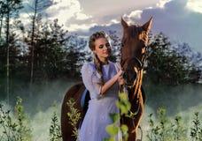 白色礼服的妇女走与马的在绿色乡下 库存图片