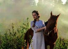 白色礼服的妇女走与马的在绿色乡下 免版税库存照片