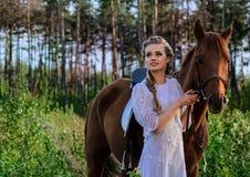 白色礼服的妇女走与马的在绿色乡下 免版税库存图片