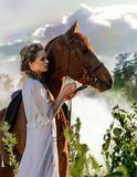 白色礼服的妇女走与马的在绿色乡下 图库摄影