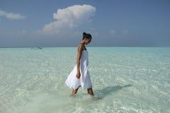 白色礼服的妇女走在透明水中的 库存照片