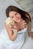白色礼服的孕妇有海海扇壳的 免版税图库摄影