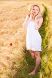 白色礼服的孤独的美丽的年轻白肤金发的女孩有草帽的 免版税库存图片