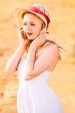 白色礼服的孤独的美丽的年轻白肤金发的女孩有草帽的 库存照片