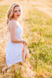 白色礼服的孤独的美丽的年轻白肤金发的女孩有草帽的 库存图片