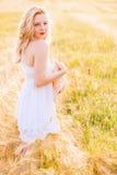 白色礼服的孤独的美丽的年轻白肤金发的女孩有草帽的 免版税库存照片