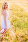 白色礼服的孤独的美丽的年轻白肤金发的女孩有草帽的 免版税图库摄影