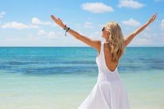 白色礼服的少妇享受在海滩的夏日 免版税库存图片