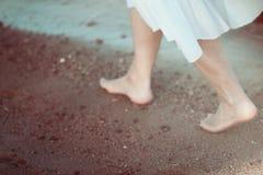 白色礼服的少妇单独走在海滩的 免版税库存图片
