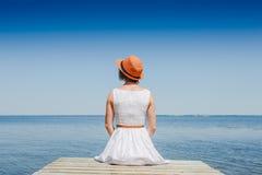 白色礼服的少妇晒日光浴在海边的 免版税库存照片