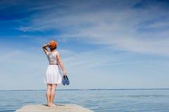 白色礼服的少妇晒日光浴在海边的 免版税库存图片