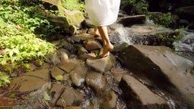 白色礼服的年轻可爱的妇女赤足走在道路的到小瀑布在热带雨林密林 无忧无虑 股票录像