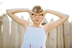白色礼服的年轻试验女孩假装飞行-假玻璃的 免版税库存图片