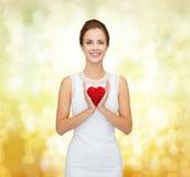 白色礼服的微笑的妇女有红色心脏的 免版税库存照片