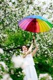 白色礼服的微笑的站立在开花的女孩和彩虹起动从事园艺与五颜六色的彩虹伞 库存照片