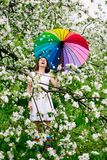 白色礼服的微笑的站立在开花的女孩和彩虹起动从事园艺与五颜六色的彩虹伞 免版税库存图片