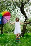 白色礼服的微笑的站立在开花的女孩和彩虹起动从事园艺与五颜六色的彩虹伞 免版税图库摄影
