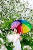 白色礼服的微笑的站立在开花的女孩和彩虹起动从事园艺与五颜六色的彩虹伞 免版税库存照片