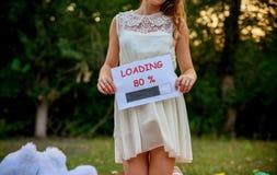 白色礼服的怀孕的妻子 免版税库存照片