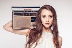 白色礼服的性感的女孩拿着一台减速火箭的收音机 库存图片