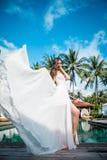 白色礼服的性感的新娘在豪华旅游胜地 时尚在风的礼服飞行 浪漫妇女松弛近的游泳池 库存图片