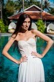 白色礼服的性感的新娘在豪华旅游胜地 浪漫妇女松弛近的游泳池 免版税图库摄影