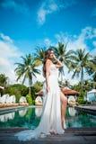 白色礼服的性感的新娘在豪华旅游胜地 浪漫妇女松弛近的游泳池 免版税库存照片