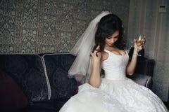 白色礼服的性感的深色的新娘有香槟玻璃的 免版税库存照片