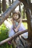 白色礼服的恼怒的小女孩在森林森林若虫 晴朗的日 免版税库存照片