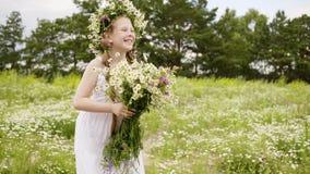 白色礼服的愉快的儿童女孩有花束的和雏菊在花草甸缠绕 股票视频
